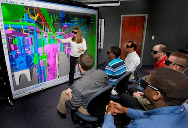 Newport News Shipbuilding's Tosha Revere, demonstrates three dimensional Immersive Visualization techniques using a Rapid Operational Virtual Reality ROVR system, 5/26/2009.