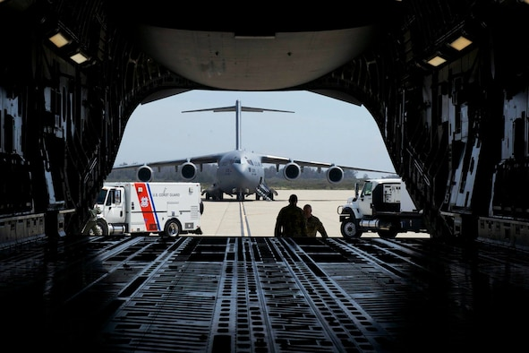 An Air Force C-17 and Coast Guard vehicle can be seen through the cargo bay of another Air Force C-17.