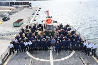 Coast Guard Cutter Bear (WMEC-901) crewmembers stand among interdicted drugs on the flight deck of the cutter April 18, 2019 at Port Everglades, Florida.