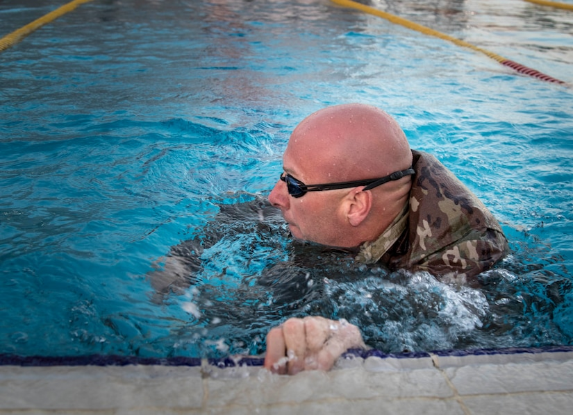 Army Maj. Brian Pranske, 108th Sustainment Brigade, Illinois Army National Guard, turns to swim another lap during the swim event of the German Armed Forces Badge (GAFB) for Military Proficiency on April 8, 2019, at Camp Arifjan, Kuwait. During this event, service members must swim 100 meters in uniform within four minutes and then remove their uniform in the deep end without support. U.S. Army Central hosts events such as the GAFB to enhance service member's personal abilities to stay combat ready which improves overall capabilities.