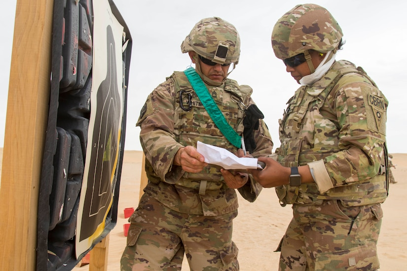 Army Sgt. Tadalies Sanchez, right, 637th Chemical, Biological, Radiological and Nuclear Company, reviews her scorecard with her grader, Staff Sgt. Jonathan White, 300th Sustainment Brigade, after firing a Beretta M9 during the range qualification event of the German Armed Forces Badge (GAFB) for Military Proficiency on April 9, 2019, at Udairi Range, Kuwait. During this event, participants stand and shoot a total of five rounds with a Beretta M9 at three silhouettes. Participants, who must hit each target at a minimum, shoot in order at targets one, two, three, one, two. Competitors earn bronze with three hits, silver for four hits and gold for five hits. U.S. Army Central hosts events such as the GAFB to enhance service member's personal abilities to stay combat ready which improves overall capabilities.