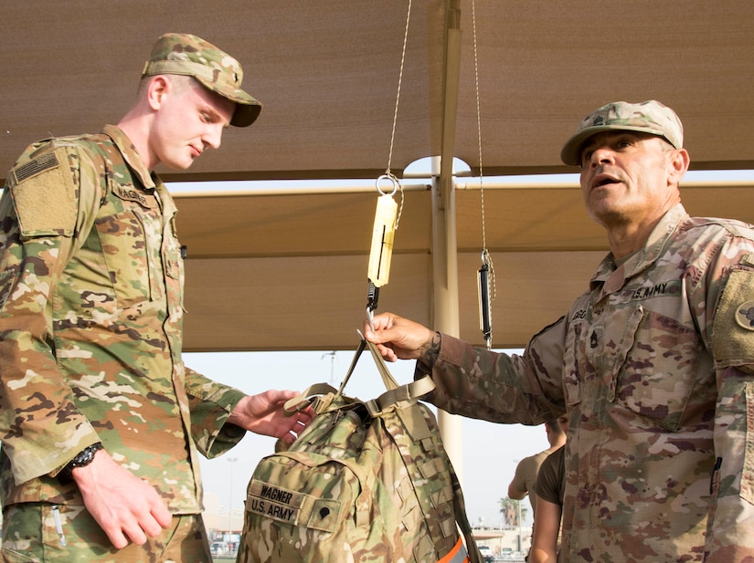 Army Spc. Darth Wagner, a human resources specialist with U.S. Army Central, watches as grader, Sgt. 1st Class Al Gagow, 1st Theater Sustainment Command, weighs his ruck sack during the ruck march event of the German Armed Forces Badge (GAFB) for Military Proficiency on April 11, 2019, at Camp Arifjan, Kuwait. During this part of the event, participants ruck march with a ruck sack weighing at least 33 pounds, not including food or water. Participants, preassigned a maximum distance based on prior performance, may earn gold for completing 12 kilometers within 120 minutes, silver for 9 kilometers within 90 minutes or bronze for 6 kilometers with 60 minutes. U.S. Army Central hosts events such as the GAFB to enhance service members' personal abilities to stay combat ready which improves overall capabilities.