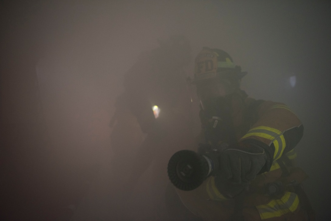 Airmen simulate extinguishing a fire