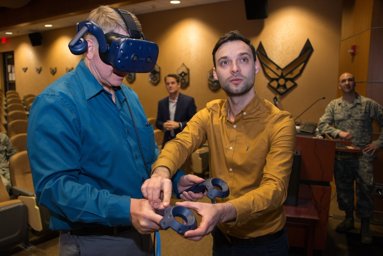 Jeffrey Fries, 1st Weather Group director of operations, learns to use virtual reality controllers from Dainius Slavinskas, technical director at Myriad Global Media, during a product handover March 14, 2019, at Offutt Air Force Base, Nebraska. 1st WXG fielded a virtual reality training product that will allow Air Force weather personnel to familiarize themselves with a tactical meteorological observation system, known as a TMQ-53. (U.S. Air Force photo by Paul Shirk)