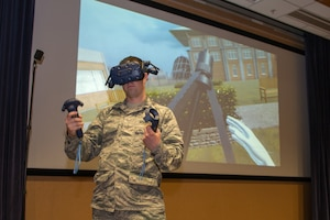 Capt. Matthew Perkins, 1st Weather Group science officer, sets up a tripod in virtual reality during a product handover March 14, 2019, at Offutt Air Force Base, Nebraska. The 1st WXG VR training software allows Airmen to train in locations where equipment may not be readily available and reduces wear and tear on actual equipment. (U.S. Air Force photo by Paul Shirk)