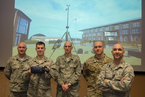 Airmen from the 1st Weather Group pose for a group photo in front of a projection of a new virtual reality training system March 14, 2019, at Offutt Air Force Base, Nebraska. The VR trainer uses off-the-shelf computing hardware, making it easier for other units that wish to adopt the technology. (U.S. Air Force photo by Paul Shirk)