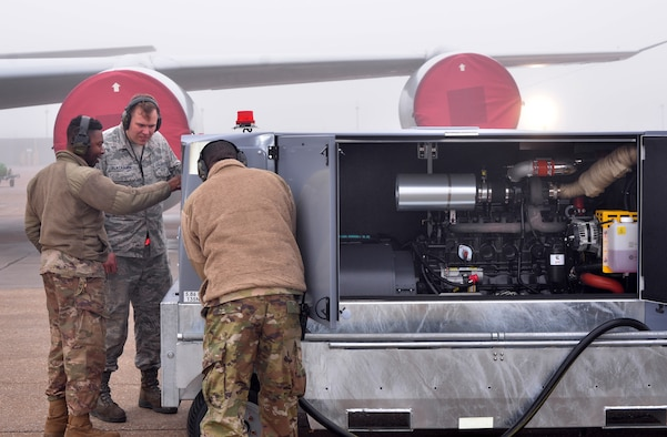 Staff Sgt. David Blackburn, 55th Maintenance Squadron aerospace ground equipment (AGE) journeyman, center, and other AGE personnel, look over recently acquired generators on Offutt AFB, Nebraska. (U.S. Air Force photo by D.P. Heard)