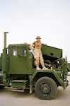Staff Sgt. Mary Junell stands on her assigned truck while she was serving in Iraq in 2004 with the North Carolina National Guard's 1450th Transportation Company. The unit spent several months on the roads in Iraq before they were able to get armor on their vehicles; a common occurrence in the early years of Operation Iraqi Freedom.