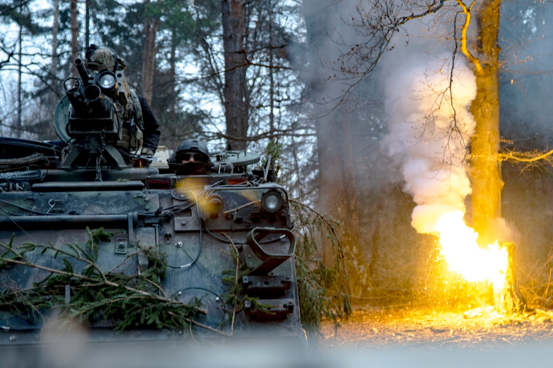 A tank rolls toward the camera as a tree burns in the background.