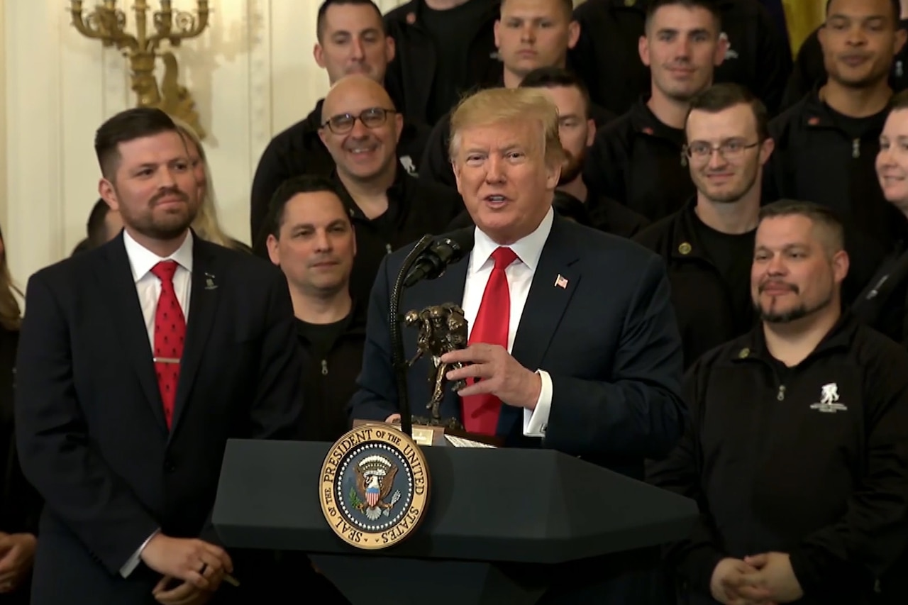 "President Trump speaks at podium in front of Wounded Warrior ""Soldier Ride"" participants"