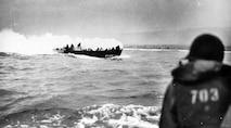 A burning landing craft approaches the Omaha beachhead.