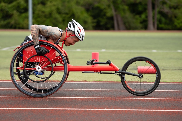 An athlete steers a handcycle on a track.