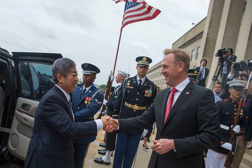 Acting Defense Secretary Patrick M. Shanahan shakes hands with the Japanese defense minister with service members in the background.