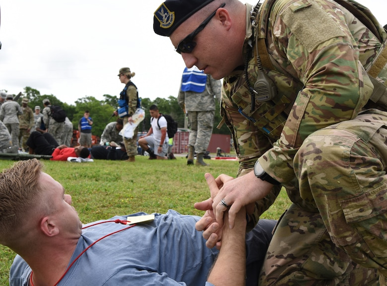 "U.S. Air Force Tech. Sgt. Jared Miller 81st Security Forces Squadron flight sergeant, provides medical assistance to Staff Sgt. Colton Monnin, 81st Medical Operations Squadron medical technician, as he portrays a ""victim"" during a mass casualty and response exercise on Keesler Air Force Base, Mississippi, April 17, 2019. The scenario for the two-day event included a simulated plane crash with debris landing both on and off base in crowds of people. The exercise tested base and local civilian emergency response organizations' ability to operate in a multi-agency and multi-jurisdiction crisis situation. (U.S. Air Force photo by Kemberly Groue)"