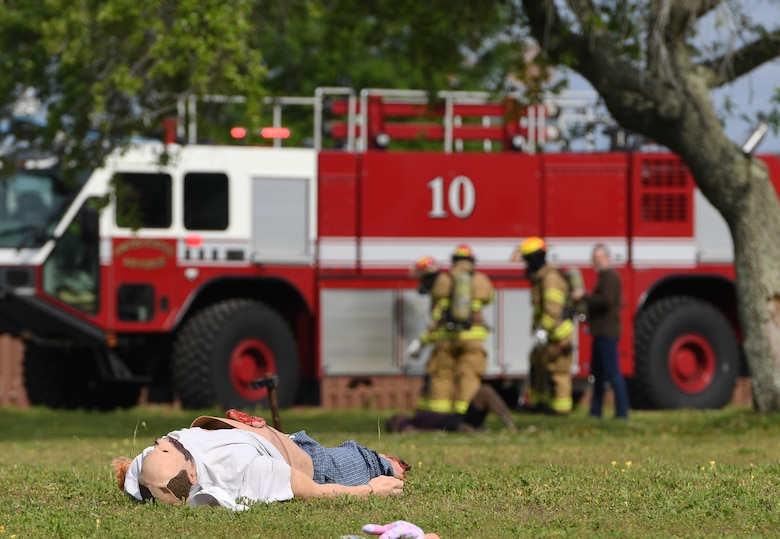 "A mannequin portraying a ""victim"" lies on the ground as Keesler firefighters arrive on scene during a mass casualty and response exercise on Keesler Air Force Base, Mississippi, April 17, 2019. The scenario for the two-day event included a simulated plane crash with debris landing both on and off base in crowds of people. The exercise tested base and local civilian emergency response organizations' ability to operate in a multi-agency and multi-jurisdiction crisis situation. (U.S. Air Force photo by Kemberly Groue)"