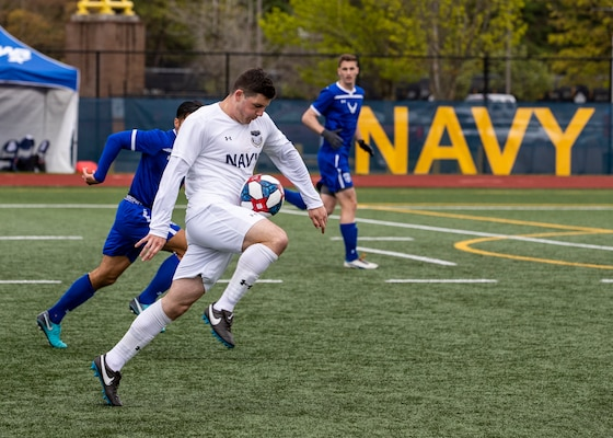 NAVAL STATION EVERETT, Wa. (April 18, 2019) - Seaman Daniel Galvin, stationed at Naval Weapons Station Earle, N.J., drives the ball past defenders from the Air Force soccer team at the Armed Forces Sports Men's Soccer Championship hosted at Naval Station Everett. (U.S. Navy Photo by Mass Communication Specialist 2nd Class Ian Carver/RELEASED).