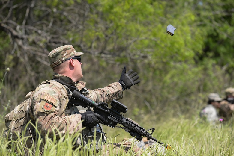 Staff Sgt. Codey Doehrmann, 47th Security Forces Squadron military working dog handler, catches a fresh magazine during an exercise at Laughlin Air Force Base, Texas, April 17, 2019. As the exercise drew near its end, so did many of the ammo pouches Laughlin's Defenders depended on, but Doehrmann could count on his wingmen. (U.S. Air Force photo by Senior Airman Benjamin N. Valmoja)