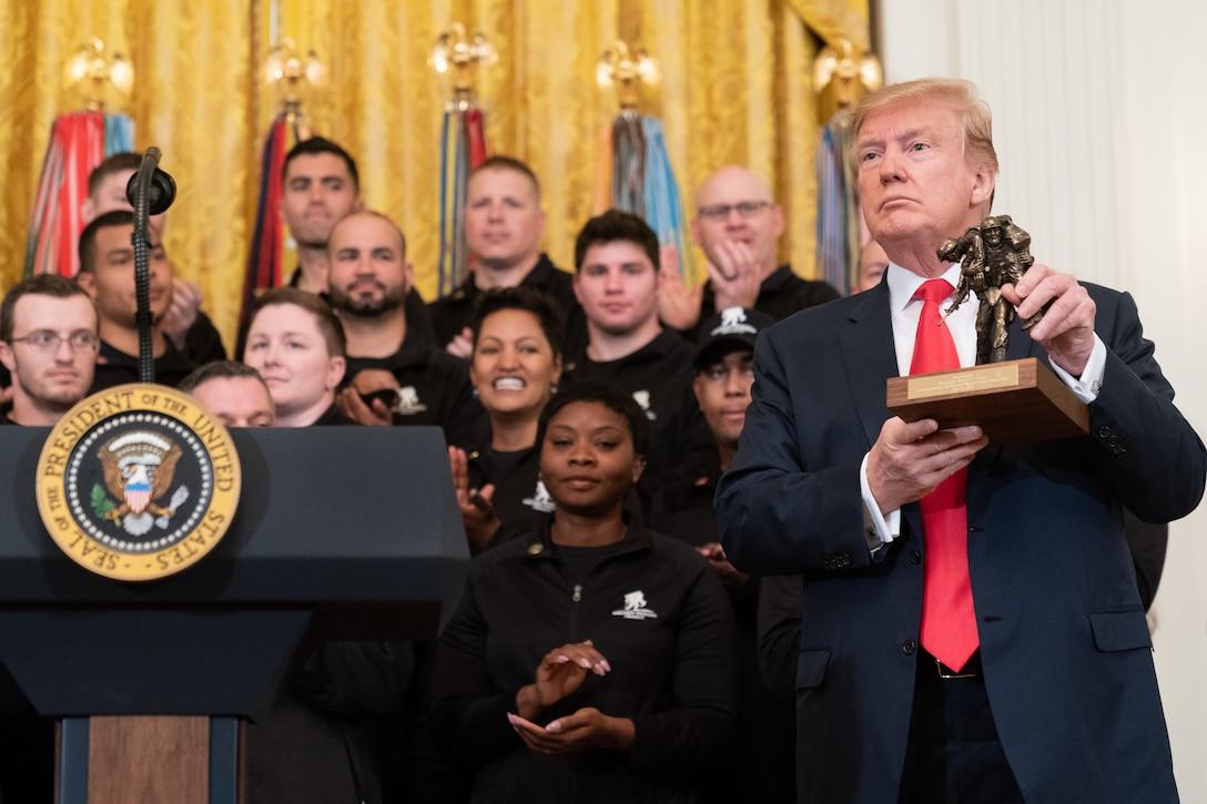 President Trump holds a figurine.
