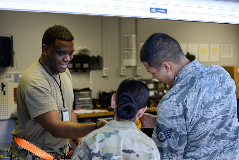 Staff Sgt. Carlyn Ramos, an integrated instument and flight control systems craftsman (middle) and Staff Sgt. Nicholas Espinoza, an aircraft electrical and environmental systems technician (right), both assigned to the 735th Air Mobility Squadron, check out tools from Staff Sgt. Emir Murphy (left), CTK Section Custodian assigned to the 735th Air Mobility Squadron inside Hangar No. 9 at Joint Base Pearl Harbor-Hickam, Hawaii April 16, 2019. The 735th Air Mobility Squadron ensures incoming aircraft can complete their missions in the Pacific region. (U.S. Air National Guard photo by Staff Sgt. Steven Tucker)