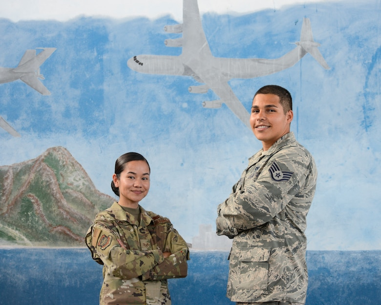 Staff Sgt. Carlyn Ramos, an integrated instument and flight control systems craftsman (left) and Staff Sgt. Nicholas Espinoza, an aircraft electrical and environmental systems technician (right), both assigned to the 735th Air Mobility Squadron, pose in front of a mural inside Hangar No. 9 at Joint Base Pearl Harbor-Hickam, Hawaii April 16, 2019. The 735th Air Mobility Squadron ensures incoming aircraft can complete their missions in the Pacific region. (U.S. Air National Guard photo by Staff Sgt. Steven Tucker)