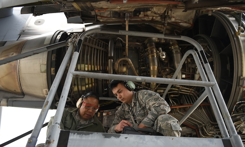 Master Sgt. Ruel Lechadores, 446th Aircraft Maintenance Squadron crew chief, and Airman 1st Class Ryan Watts, 62nd Aircraft Maintenance Squadron crew chief, communicate and work to repair an engine on a C-17 Globemaster III, April 3, 2019, on March Air Reserve Base in California.