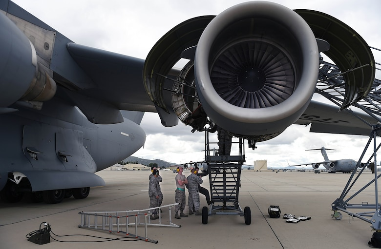 Several crew chiefs from the 62nd Aircraft Maintenance Squadron work to repair the engine of C-17 Globemaster III on March Air Reserve Base in California, April 3, 2019.