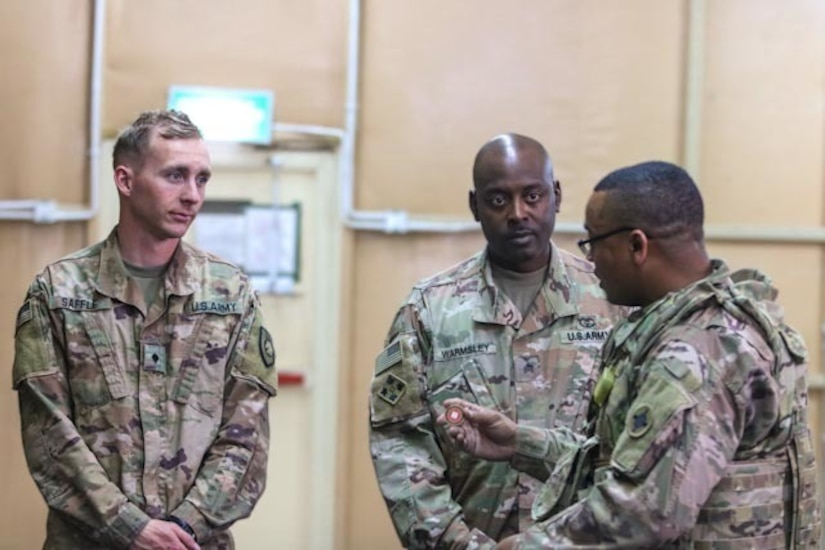 Sgt. 1st Class Joey Tribble, 184th Sustainment Command, presents challenge coins to Sgt. Toree Warmsley and Spc. Jonathan Saffle, 300th Sustainment Brigade combat lifesaver instructors, during the Combat Lifesaver course held at Camp Arifjan, Kuwait, April 19, 2019.