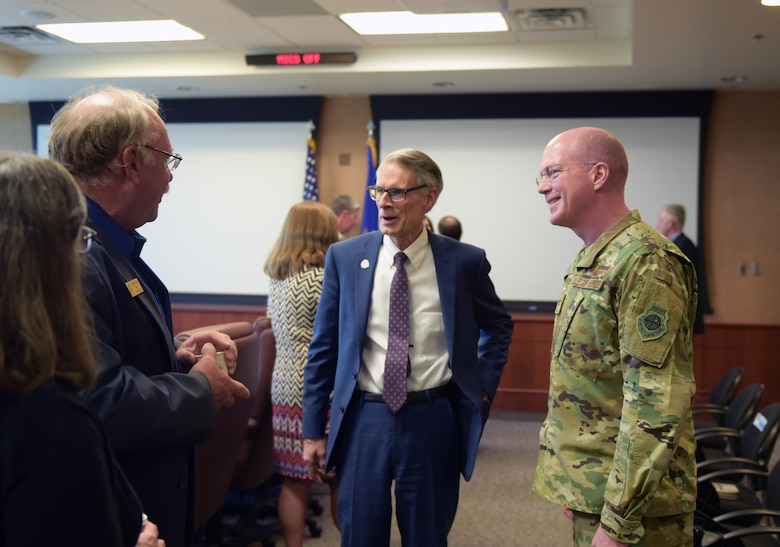From left to right, Bob Muckle, mayor of Louisville, Bob LeGare, mayor of Aurora, and Col. Troy Endicott, 460th Space Wing commander, greet one-another at the Mayors Day at Buckley Air Force Base, Colorado, April 19, 2019.