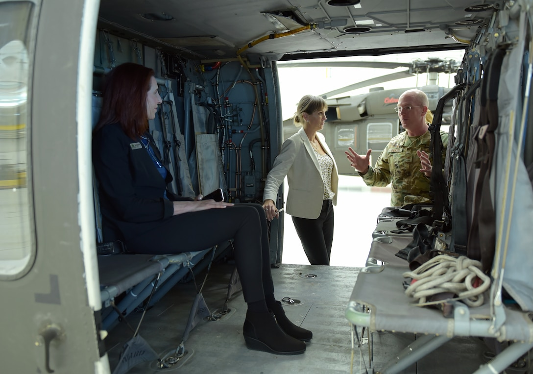 From right to left, Col. Troy Endicott, 460th Space Wing commander, Catherine Marinelli, Metro Mayor Caucus director and Tera Radloff, Castle Pines mayor, talk inside a UH-60 Black Hawk at Buckley Air Force Base, Colorado, April 19, 2019.