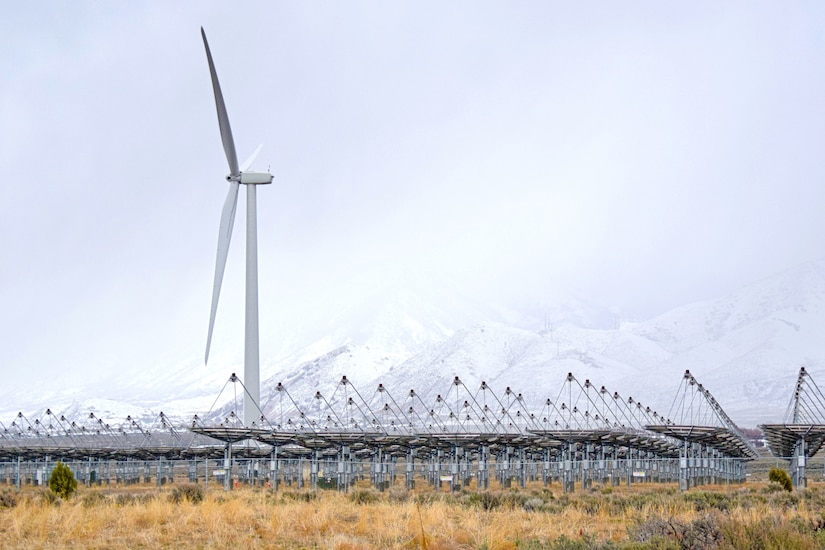 A wind turbine and solar arrays grace desert.