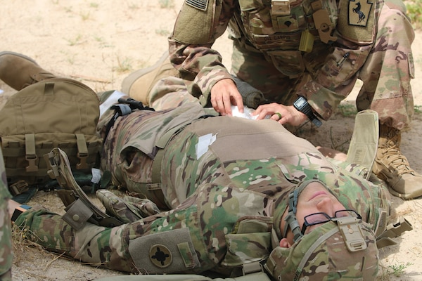 Spc. Sasha Del Carpio Torres, 28th Military Police Company, treats a wound on a mock casualty during a Combat Life Saver course held by the 300th Sustainment Brigade at Camp Arifjan, Kuwait, April 19, 2019.