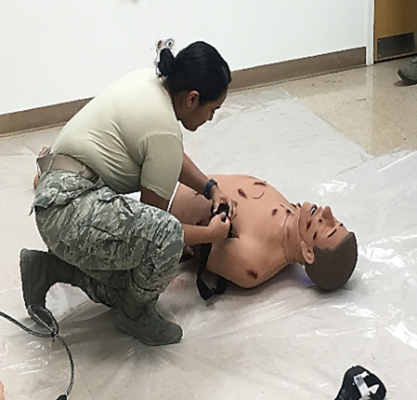 Staff Sgt. Taylor Lopez Boodooram, Active Duty Clinic Office manager, demonstrates tourniquet placement on a manikin's arm during a National Association of Emergency Medical Technicians Tactical Combat Casualty Care course in the 366th Medical Group Simulation Lab Room at Mountain Air Force Base, Idaho, February 2019. TCCC is a standardized course offered across the military to equip warfighters with basic skills to save lives in combat operations. (Courtesy photo)