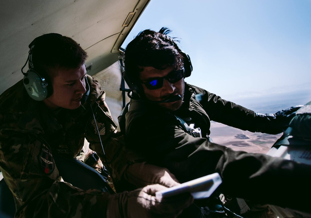 U.S. Air Force Tech. Sgt. Brian Wahl with the  Train, Advise, Assist Command-Air, as part of Resolute Support Mission, goes through a pre-drop checklist with an Afghan counterpart to practice air drops near Kabul, Afghanistan, March 19, 2017. The TAAC-Air advisors foster working relationships and fortify confidence in the mission. (U.S. Air Force photo by Senior Airman Jordan Castelan)