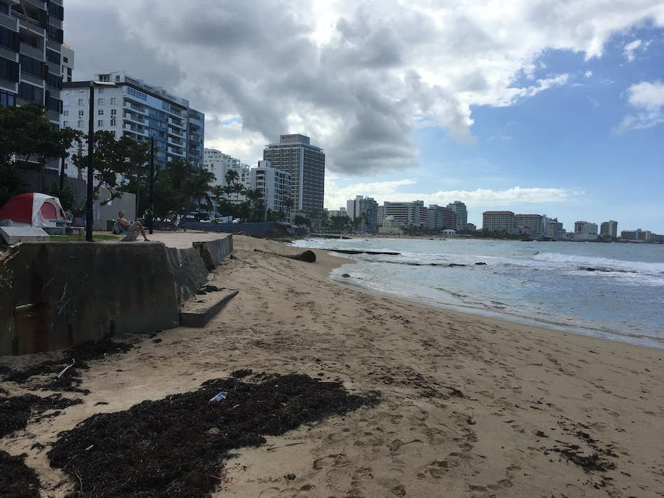 Beach sand with water on the right and buildings on the back in San Juan, Puerto Rico