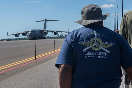 A chaperone for the Take Flight Aviation Camp walks towards a C-17 Globemaster III April 18, 2019, at Joint Base Charleston, S.C.