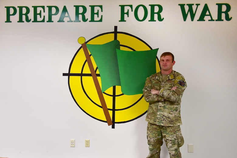 A man wearing the operational camouflage pattern uniform stand with his arms folded in front of a mural of a gren flag.