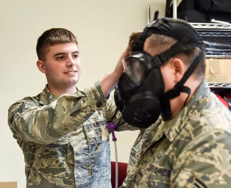 A man wearing the Airman Battle Uniform fits a gas mask on another man wearing the Airman Battle Uniform.