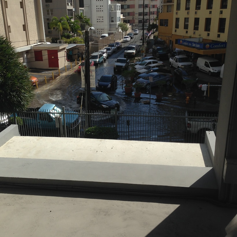 several cars in flooded street viewed from a balcony in San Juan, Puerto Rico