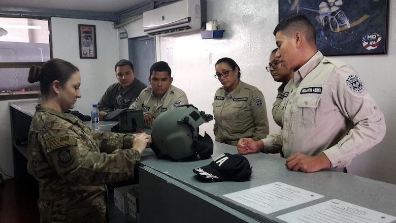 Master Sgt. Natasha Titemore, 571st Mobility Support Advisory Squadron Aircrew Flight Equipment instructor, demonstrates the capabilities of a HGU-56/P helicopter helmet to members of the Costa Rican Air Vigilance Service, March 29, 2019.  The SVA members completed the 2-week course in preparation of their new established AFE work-center in the Base 2 facilities located at the Juan Santamaria International Airport in Costa Rica. (U.S. Air Force photo by Master Sgt. Robert Ramirez)