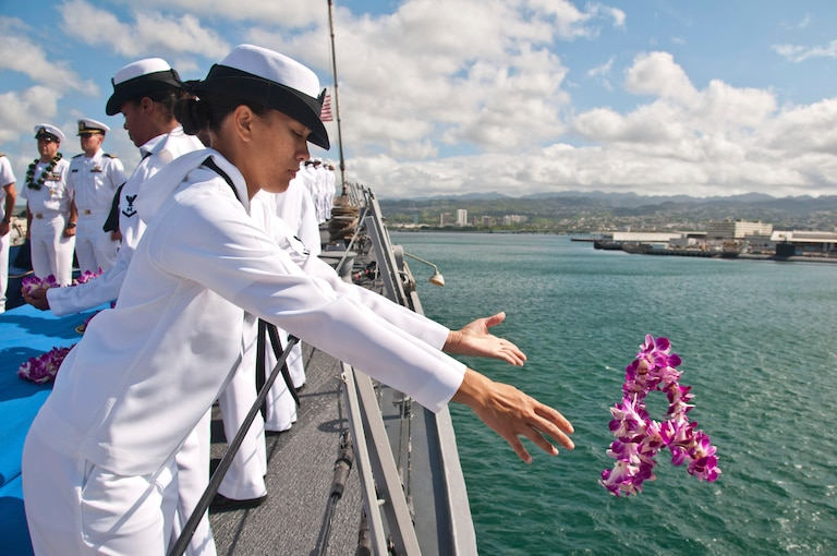 A sailor drops a lei into the ocean from the deck of a ship.