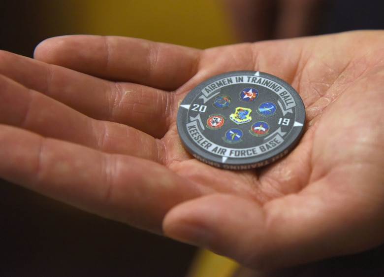 U.S. Air Force Tech. Sgt. Zachary Bartlett, 81st Training Group Airman transition assistance flight flight chief, displays a chip commemorating the Airmen In Training Ball at the Bay Breeze Event Center on Keesler Air Force Base, Mississippi, April 19, 2019. The event, hosted by the 81st TRG, is the first of its kind and was geared toward training Airmen on how to participate and act during a formal military ball so they can feel confident in their abilities when arriving at their follow-on locations. The Airmen served in key positions throughout the ball such as emcees, color guard, POW/MIA table ceremony, national anthem singer and the invocation. (U.S. Air Force photo by Kemberly Groue)
