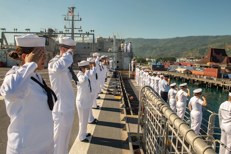 DILI, Timor-Leste (April 22, 2019) – Pacific Partnership 2019 personnel salute while manning the rails of the fast expeditionary transport ship USNS Fall River (T-EPF 4) during its arrival in Timor Leste. Pacific Partnership, now in its 14th iteration, is the largest annual multinational humanitarian assistance and disaster relief preparedness mission conducted in the Indo-Pacific. Each year the mission team works collectively with host and partner nations to enhance regional interoperability and disaster response capabilities, increase security and stability in the region, and foster new and enduring friendships in the Indo-Pacific.