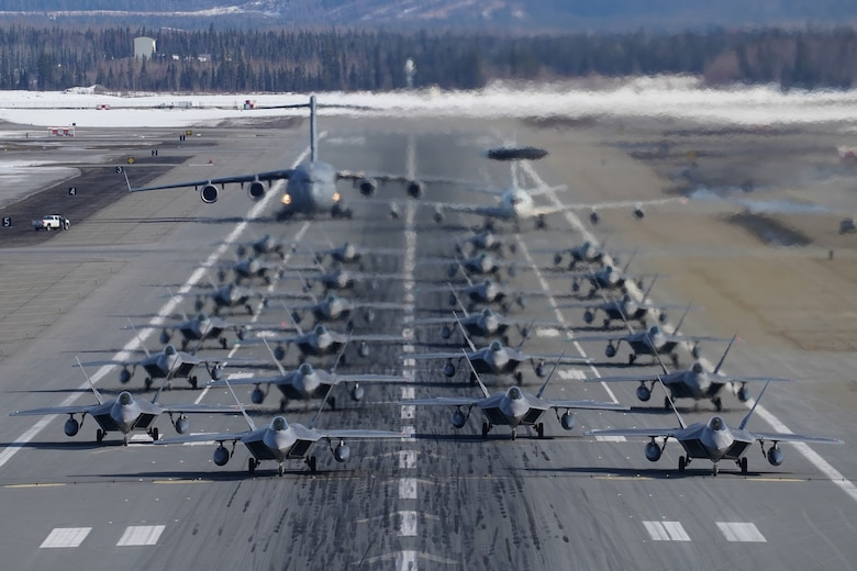 Twenty-four F-22 Raptors from 3rd Wing and 477th Fighter Group, a C-17 Globemaster III and an E-3 Sentry participate in a close formation taxi, known as an Elephant Walk, March 26, 2019, during a Polar Force exercise at Joint Base Elmendorf-Richardson, Alaska. This two-week exercise gives squadrons an opportunity to demonstrate their abilities to forward deploy and deliver overwhelming combat power. (U.S. Air Force photo/Justin Connaher)