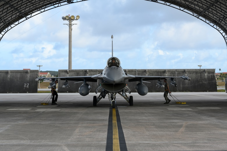 U.S. Air Force crew chiefs assigned to the 35th Fighter Wing put chocks down to secure a U.S. Air Force F-16 Fighting Falcon at Andersen Air Force Base, Guam, April 22, 2019.