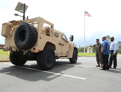 A Marine and civilian-Marines discuss the capabilities of the Joint Light Tactical Vehicle, which will take place of the Humvee, during a roadshow in front of Marine Corps Logistics Command Headquarters, April 9.