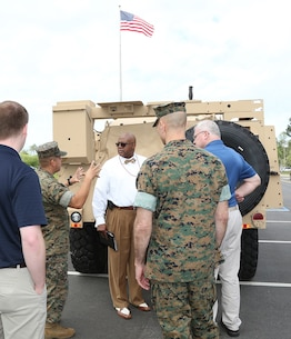 Marines and civilian-Marines discuss the capabilities of the Joint Light Tactical Vehicle, which will take place of the Humvee, during a roadshow in front of MARCORLOGCOM Headquarters, April 9.