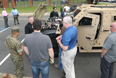 Marine Corps Logistics Command civilian-Marines look at the new Joint Light Tactical Vehicle that will take place of the Humvee during a roadshow in front of MARCORLOGCOM Headquarters, April 9.