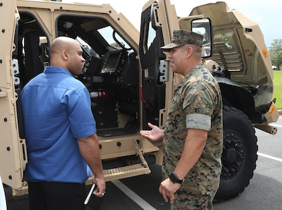 A Marine and civilian-Marine discuss the capabilities of the Joint Light Tactical Vehicle, which will take place of the Humvee, during a roadshow in front of Marine Corps Logistics Command Headquarters, April 9.