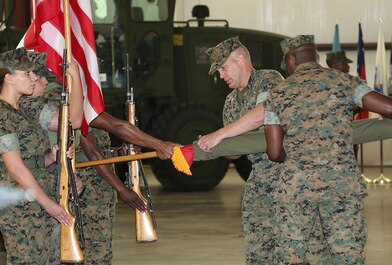 Col. Kipp Wahlgren, center, commanding officer, and 1stSgt. Kevin Davis, right, senior enlisted advisor, both with Marine Force Storage Command, uncase the unit colors during MFSC's activation ceremony held aboard Marine Corps Logistics Base Albany, Ga., April 11.