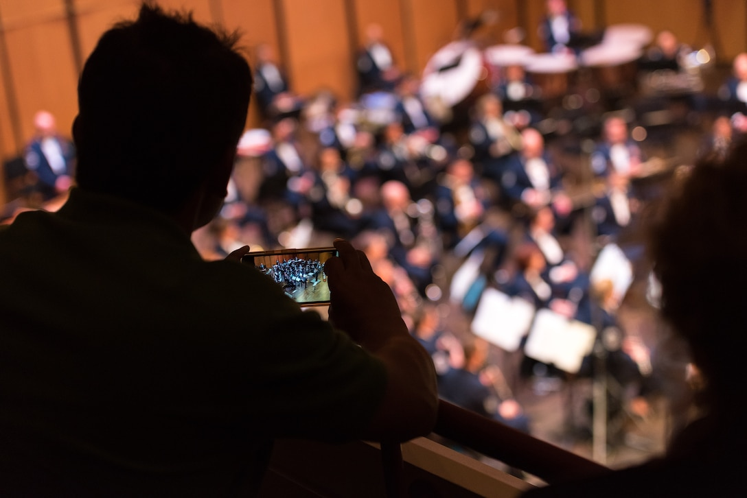 An audience member snaps a picture of the Concert Band on Apr. 18, during the final concert of The U.S. Air Force Band's 2019 Guest Artist Series. The concert featured internationally acclaimed saxophonist Joe Lulloff. (U.S. Air Force photo by Master Sgt. Grant Langford)